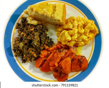 Comfort food. A serving of kale greens with smoked turkey, candied yams, macaroni and cheese, cornbread on a white and blue plate. Top view.