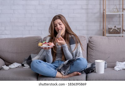 Comfort foods and stress eating concept. Frustrated young lady devouring pastry on sofa at home. Upset woman dealing with negative emotions, anxiety or problems through sweets
