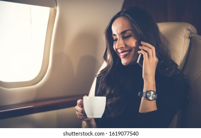 Comfort lover. Close-up photo of an elegant woman with long dark hair, who is talking on the phone and enjoying a cup of coffee during the flight.