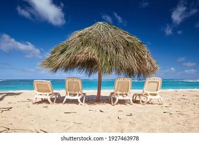 comfort on a tropical beach. palm umbrella and sunbeds.