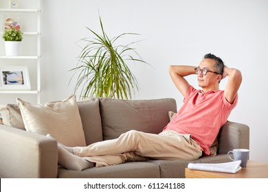 comfort and people concept - man in glasses relaxing on sofa at home