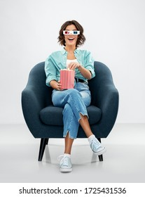 comfort, people and furniture concept - portrait of happy smiling young woman in 3d movie glasses eating popcorn from striped bucket sitting in modern armchair over grey background