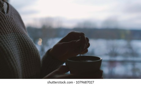 comfort relaxation leisure. girl drinking tea at home at dusk. romantic calm twilight atmosphere. evening ritual to recharge energy regain strength