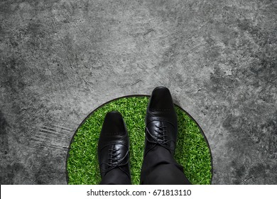 Comfort Zone concept, Businessman with black Oxford shoes steps over circle line to outside bound, Top view, Grunge Dirty Concrete Floor as Background