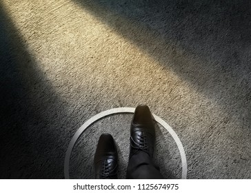 Comfort Zone Concept. Businessman with Formal Shoes Steps over Circle Line to Outside the White Bound. Top View, Dark Tone, Light Shading on Cement Floor