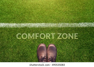 Comfort Zone Concept, Male with Leather Shoes Standing behind a line on Green Grass Field with word : Comfort Zone, Top view