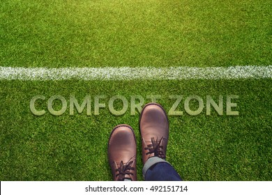 Comfort Zone Concept, Male with Leather Shoes Steps over a word with line on Green Grass Field, Top view