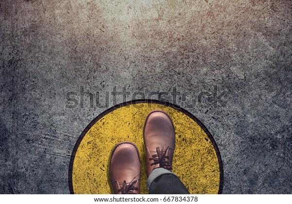 Komfort Zone Konzept, Männchen mit Lederschuhen Stufen über eine kreisrunde Linie nach außen, Draufsicht und dunkler Ton, Grunge Dirty Beton Boden als Hintergrund