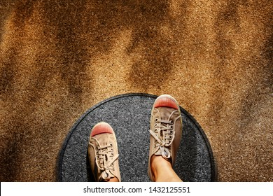 Comfort Zone Concept. Male on Sneaker Shoes Steps over Circle Line to Outside Bound, Top View, Grunge Dirty Concrete Floor with Sunlight as background