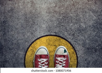 Comfort Zone Concept. Street Sneaker Shoes Standing inside a Circle Bound, Top view and Dark tone, Grunge Dirty Concrete Floor as Background