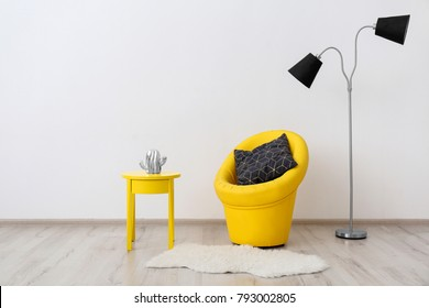 Comfortable armchair, floor lamp and side table near white wall