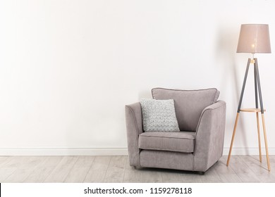 Comfortable armchair and lamp near wall with space for design. Stylish interior elements