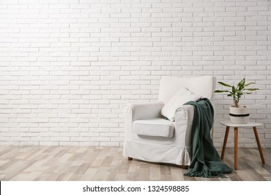 Comfortable armchair near brick wall in modern room interior. Space for text