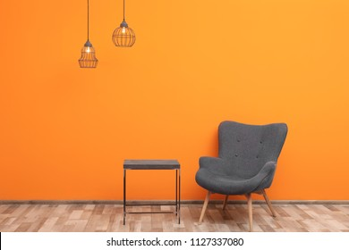 Comfortable armchair and small table against color wall