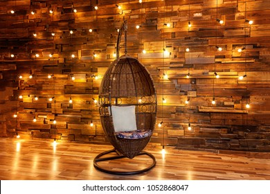 Comfortable armchair swing hanging light bulb over the wooden background, mockup poster. Background wood planks with lamps