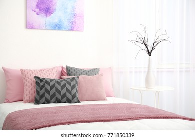 Comfortable bed with cushions in room