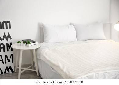 Comfortable bed in light room interior