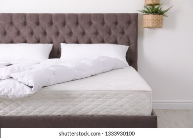 Comfortable bed with new mattress in room. Healthy sleep