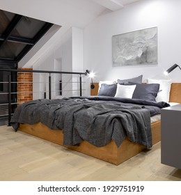 Comfortable bed on modern attic bedroom on mezzanine floor in loft style apartment with big window and white walls