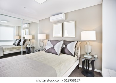 Comfortable bed and pillows with lamps in bedroom, bed has pillows and sheets, lamp table near bed, glass mirror near to bed, ceiling is white color, fully air conditioned room with luxurious look.