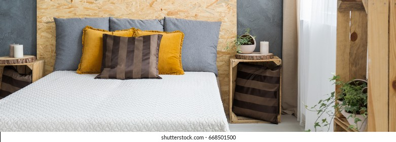 Comfortable bed with pillows and wooden osb headboard