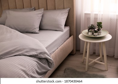 Comfortable bed with soft blanket near window indoors