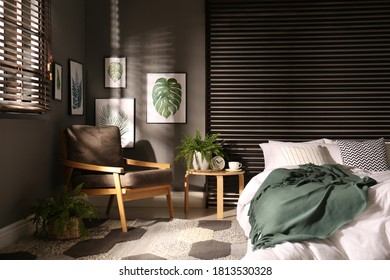 Comfortable bedroom with armchair and pictures on wall. Interior design