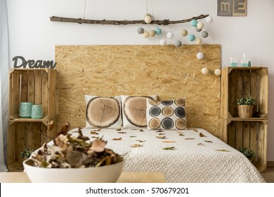 Comfortable beige double bed with DIY bedside cabinets made from wooden boxes