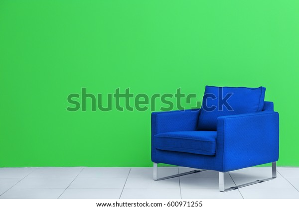Comfortable blue armchair on green wall background