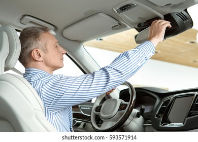 Comfortable car. Mature businessman sitting in a car at the dealership adjusting rearview mirror copyspace comfort business buying a car driving driver travel auto vehicle luxury consumerism concept