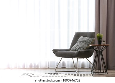 Comfortable chair near window with elegant curtains in room. Space for text