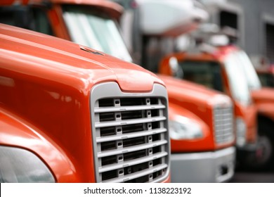 Comfortable and compact middle sized rigs semi trucks standing in row in warehouse dock for loading cargo for local shipping and deliveries commercial cargo to business and stores in the city limit