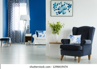 Comfortable dark blue velvet armchair with floral pillow next to small table with vase with bouquet of flowers and green leafs