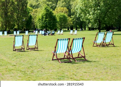 Comfortable deck chair inviting people to relax on summer day in beautiful St. James park, London, UK