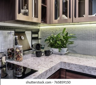 Comfortable and functional kitchen in high-tech style. Marble countertop and apron from ceramic mosaic tiles.