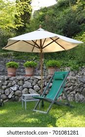 Comfortable garden chair. Garden furniture. Cozy garden design. Umbrella covering from the sun.