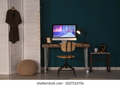 Comfortable home workplace with computer on desk against color wall