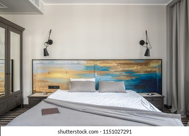 Comfortable hotel room with light walls and a striped floor. There is a double bed with a colorful wooden bedhead, dark gray nightstands and a wardrobe with mirrors, black lamps on the wall.