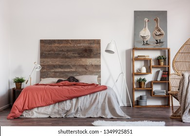 Comfortable king size bed with wooden rustic headboard and white industrial lamp next to it