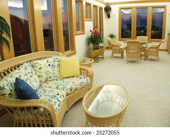 Comfortable lounge room in an expensive beach vacation home. Wicker and rattan furniture and a glass topped table decorate the interior.