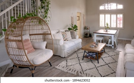 Comfortable and modern living room with light beige tones and a wicker nest chair