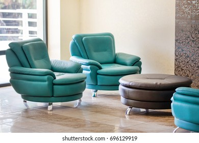 Comfortable modern luxury leather armchairs and round table in a hall or waiting area of commercial building.