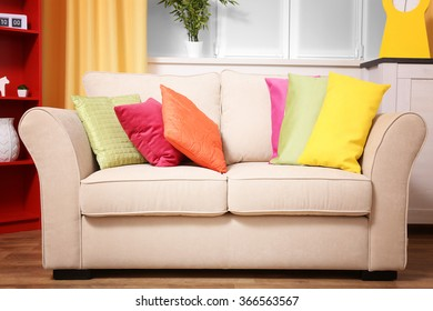 Comfortable modern sofa with bright pillows in the room, close up