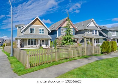 Comfortable neighborhood. Some middle class homes with nicely landscaped front yard lawn behind the wooden fence in the suburbs of the North America. Canada.