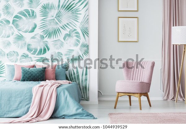 Comfortable, pale pink, upholstered chair in a cozy bedroom interior with double bed and green decorations