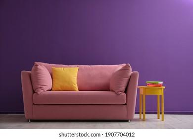 Comfortable pink sofa near purple wall in living room interior - Shutterstock ID 1907704012