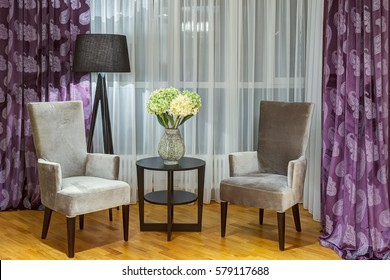 Comfortable place in bedroom with two gray velor armchairs and little rounded table. Room in gray, violet, white colors. Green and white hydrangea in vase on table. Violet curtains in print.