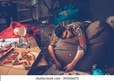 Comfortable place to pass out. Young handsome man passed out on bean bag with joystick in his hand in messy room after party