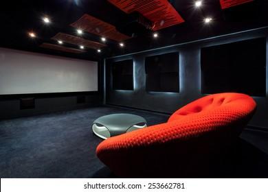Comfortable red sofa in a dark interior