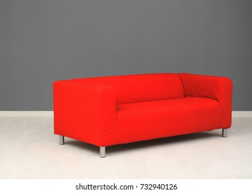 Comfortable red sofa near color wall
